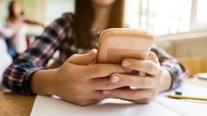Schülerin, die ihr Handy nutzt