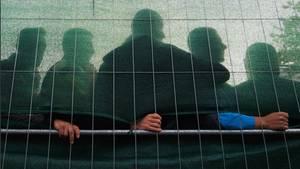 Mehrere Männer stehen hinter einem verdeckten Zaun in einer Flüchtlingsunterkunft