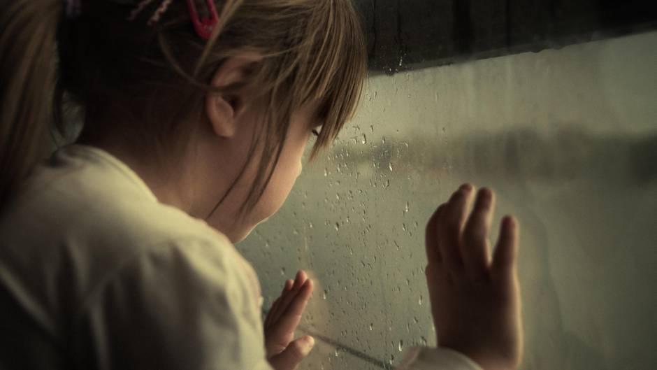 Kind steht am Fenster und guckt raus, es regnet