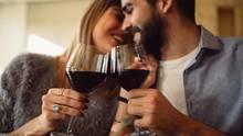 Pärchen stößt mit Rotweingläsern an