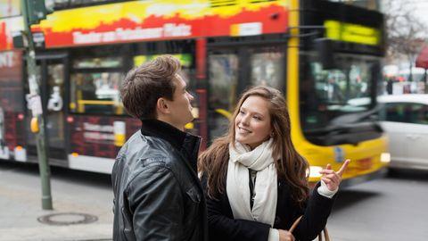Eine Frau und ein Mann kommunizieren vor einem vorbeifahrenden Bus in Berlin