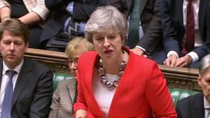 Premierministerin Theresa May steht im roten Blaser im Unterhaus und hebt beschwichtigend beide Hände