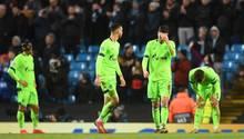 Vier Schalke-Spieler stehen niedergeschlagen auf dem Rasen bei Manchester City