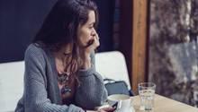 Eine Frau sitzt allein im Café und guckt aus dem Fenster