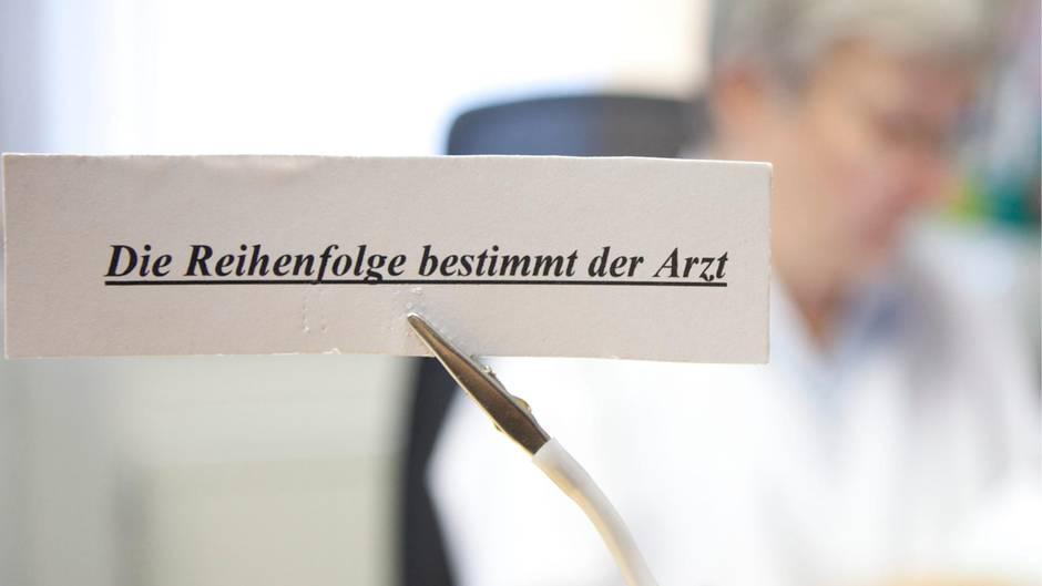Ein Schild weist in einer Arztpraxis darauf hin, dass die Reihenfolge der Patienten vom Arzt bestimmt wird