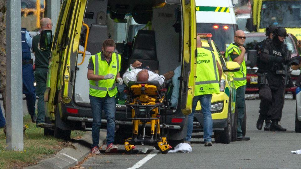 Ein Verletzter wird in Christchurch in einen Krankenwagen geladen, während schwer bewaffnete Polizisten vorbeigehen