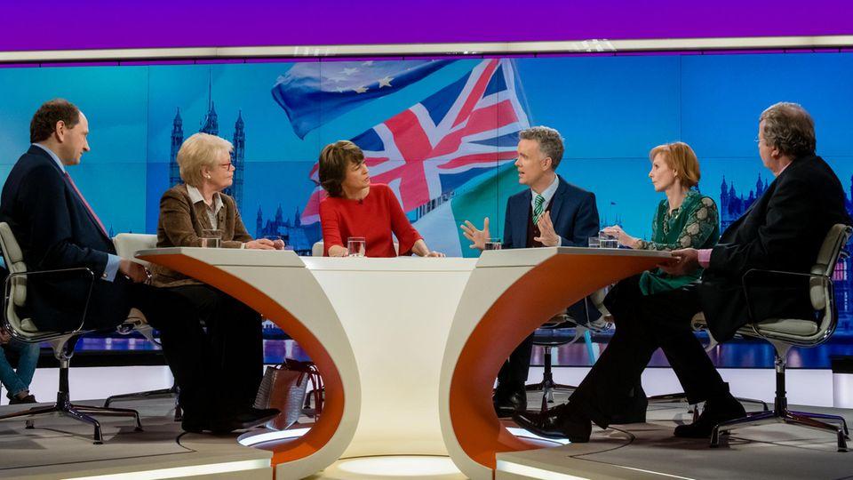 Hinter einem halbrunden Tisch sitzen links und rechts von Moderatorin Maybrit Illner zwei Frauen und drei Männer