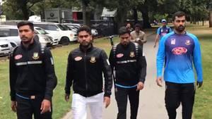 Mehrere Männer in Trainingskleidung gehen einen Weg in einem Park entlang