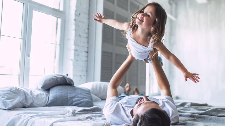 Ein Vater hebt seine Tochter in die Luft