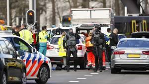 Polizisten in schwerer Montur und Sanitäter stehen zwischen Einsatzwagen am 24 Oktoberplein in Utrecht