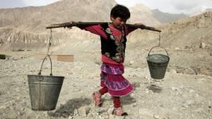 Ein Kind in der chinesischen Autonomen Region Xinjiang-Uighur holt mitEimern Wasser