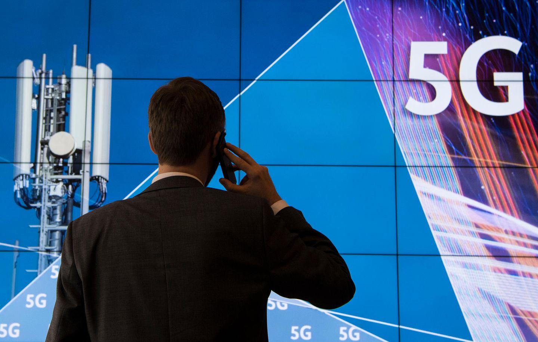 Ein Mann telefoniert vor einer Werbetafel für den 5G-Mobilfunkstandart
