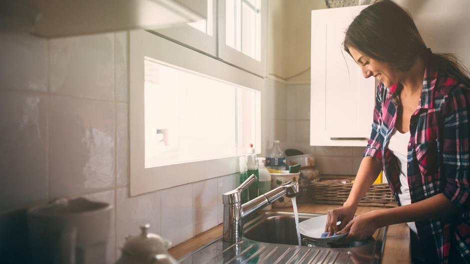 Eine Frau spült Geschirr