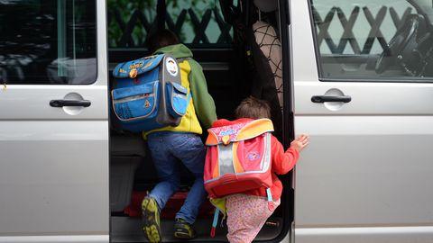 Zwei Grundschulkinder mit Ranzen auf dem Rücken steigen in die Schiebetür eines silbernen VW-Busses