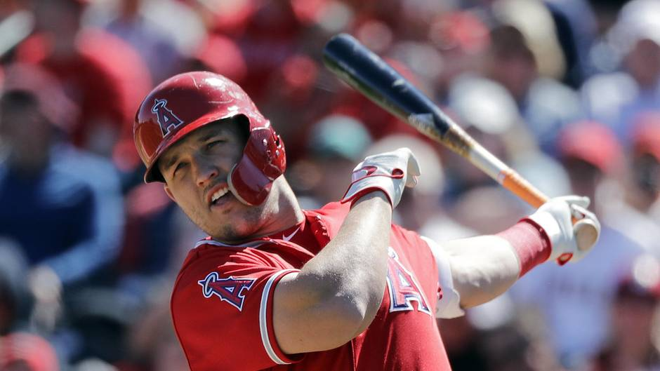 Ein Mann in rotem Baseball-Trikot und Helm lässt nach einem Schlag den Baseballschläger in seiner linken Hand ausschwingen