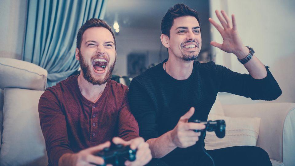 Zwei Männer spielen Playstation