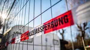 """An einem Bauzaun vor einem Campingwagen hängt rot-weißes Band mit schwarzem Aufdruck """"Polizeiabsperrung"""""""