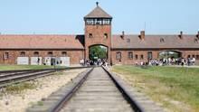 Auschwitz-Birkenau: Besucher gehen vor dem historischen Tor (Innenneite) durch das frühere Vernichtungsslager