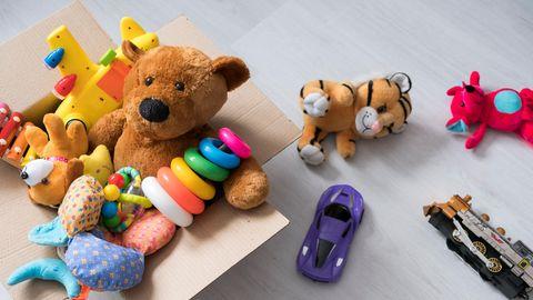 Ein Teddy sitzt in einer Box voll Spielsachen.
