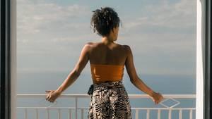 Eine Frau steht an einem Geländer und blickt auf das Meer