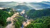 Hier wohnt der Regenmacher  Ein großes Regenwaldgebiet auf der Insel Neubritannien vor der Ostküste Papua-Neuguineas. Die aus den Bäumen aufsteigenden Nebelschwaden halten den Wald feucht und bringen jeden Tag Regengüsse, die in einem endlosen Zyklus sowohl die hydrophile Flora und Fauna als auch die Bäume selbst mit Wasser versorgen.