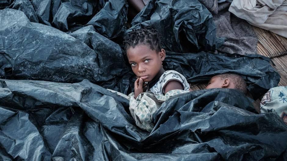 Mosambik - Hilfe - Zwei Mädchen unter Plastikplanen