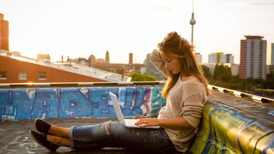 Frau sitzt auf Terrasse mit Computer