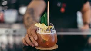Mann stellt Cocktail auf Tresen