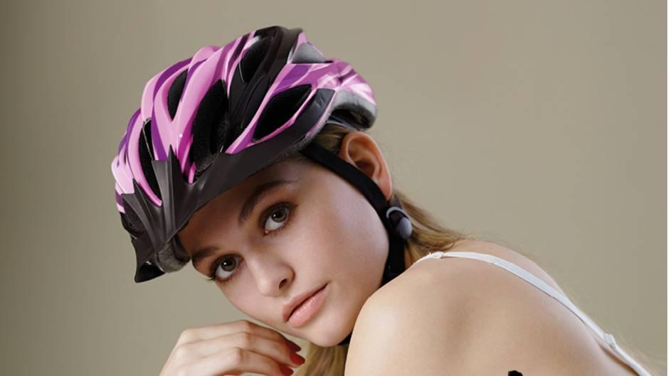 Ein Model in weißem Spitzen-BH und mit Fahrradhelm liegt auf dem Bauch und stützt sich mit den Armen auf