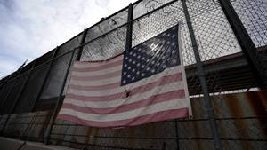 Eine US-Fahne hängt an einem Metallzaun entlang der texanisch-mexikanischen Grenze in El Paso
