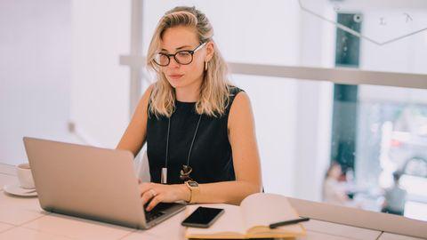 Frau mit Brille tippt auf einem Laptop