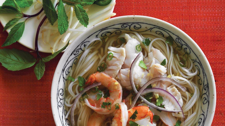 Meeresfrüchte-Pho      Zutaten:      Für die Brühe  1 knotiges, 5 cm langes Stück Ingwer, ungeschält 1 mittelgroße (270 g), gelbe Zwiebel, ungeschält, 90 g Fuji-Apfel, geschält, entkernt und in daumennagelgroße Stücke geschnitten, 2 mittelgroße Stangen Sellerie (zusammen 115 g), grob gehackt, 1 große (180 g) Karotte, in dicke Scheiben geschnitten (gebürstet und ungeschält verwenden, wenn Sie mögen), 450 g Chinakohlblätter, der Länge nach halbiert, dann quer in große Stücke geschnitten, 2 Sternanise (16 robuste Zacken), 2 ½ cm Zimtstange, 1 gehäufter TL Fenchelsamen, 1 ½ TL Koriandersamen, 1 ½ TL feines Meersalz, bei Bedarf mehr, 3 EL getrocknete Garnelen, 240 ml Muschelsaft aus der Flasche, 300 g große Garnelen mit intakten Schalen (groß, extragroß oder Riesengarnelen), 1 ½ bis 2 EL Fischsauce, etwa 1 TL Zucker oder 2 TL Ahornsirup (optional)      In die Schalen  300 g getrocknete Reisbandnudeln oder 450 g frische Pho-Nudeln, gekochte Garnelen aus der Brühe, 300 g Fischfilet, zum Beispiel Blaumaul, Schnapper, Seebarsch, Buntbarsch, Arapaima oder Lachs, ½ kleine (60 g) gelbe oder rote Zwiebel, gegen die Maserung in dünne Scheiben geschnitten und 10 Minuten in Wasser eingeweicht, 2 grüne Zwiebeln (nur grüne Teile), in dünne Scheiben geschnitten, 5 g gehacktes frisches Koriandergrün (nur die zarten oberen Stängel), 1 TL fein gehackter, geschälter Ingwer      Zubereitung:  Zubereitung der Brühe: Ingwer und Zwiebel ankohlen, schälen und zubereiten.Mit Apfel, Sellerie, Karotte und Kohl beiseitestellen. Sternanis, Zimt, Fenchel- und Koriandersamen in einen Kochtopf mit etwa 8 l Fassungsvermögen geben. Bei mittlerer Temperatur erhitzen, die Gewürze mehrere Minuten rösten, bis sie duften; dabei schütteln oder umrühren. 1 Liter Wasser hineingießen, um den Kochprozess zu stoppen. Ingwer undZwiebel sowie Apfel, Gemüse, Salz und getrocknete Garnelen dazugeben. 1 ¼ l Wasser, dann den Muschelsaft hineingießen. Teilweise zudecken und bei hoher Temperatur aufkochen. In der Zwischenz