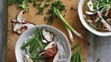 Schnelle vegetarische Pho      Zutaten:  2 cm langes, ungeschältes Stück Ingwer, 2 mittelgroße grüne Zwiebeln, 1 Sternanis (insgesamt 8 robuste Zacken), 3 ¾ cm Zimtstange, 1 oder 2 ganze Gewürznelken, 840 ml bis 1 l natriumarme oder normale Gemüsebrühe, etwa ½ TL feines Meersalz, 150 g getrocknete Reisbandnudeln, 4 Stück scharf angebratener Tofu, 8 Zuckerschoten oder dünne grüne Bohnen, 2 oder 3 frische Pilze (Shiitake, Kräuterseitling oder ähnliche), 2 bis 3 TL normale Sojasauce, etwa ½ TL Zucker oder 1 TL Ahornsirup (optional), 2 EL gehacktes frisches Koriandergrün (nur die feinen oberen Stängel), frisch gemahlener schwarzer Pfeffer (optional)      Zubereitung:  Den Ingwer schälen und in 4 oder 5 Münzen schneiden. Mit der breiten Seite eines Messers oder mit einem Fleischklopfer flach klopfen und beiseitestellen. Die grünen Teile der grünen Zwiebel in dünne Scheiben schneiden (ergibt 2 bis 3 EL) und zum Garnieren beiseitestellen. Restliche Teile in kleinfingerlange Stücke schneiden, zerquetschen, dann in den Ingwer mischen. Sternanis, Zimt und Gewürznelken in einem 3- bis 4-Liter-Topf bei mittlerer Temperatur rösten, bis sie nach 1 bis 2 Minuten duften. Ingwer und grüne Zwiebelteile dazugeben. Etwa 30 Sekunden rühren, bis sie aromatisch sind. Den Topf von der Platte schieben, 15 Sekunden abkühlen lassen, dann die Gemüsebrühe hineingießen. Den Topf wieder auf die Platte stellen, dann 480 ml Wasser und Salz dazugeben. Bei hoher Temperatur aufkochen, dann die Hitze reduzieren und 30 Minuten leicht köcheln lassen. Während die Brühe köchelt, die Reisnudeln in heißem Wasser einweichen, bis sie weich und opak sind. Abgießen, spülen und beiseitestellen. (Siehe Tipps auf Seite 38.) Nun den Tofu zubereiten. (Wenn Sie ihn im Voraus zubereiten, bei Zimmertemperatur wärmen.) Jeden fertigen Tofublock in dünne Scheiben oder in zwei große Dreiecke schneiden und beiseitestellen. Die Zuckerschoten der Länge nach halbieren oder die grünen Bohnen in kurze Teile schneiden, die Pilze i