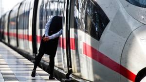 Eine Zugbegleiterin blickt amHauptbahnhof von Frankfurt am Maindurch die offene Tür eines InterCityExpress