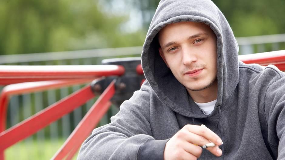 Ein Jugendlicher raucht auf einem Spielplatz