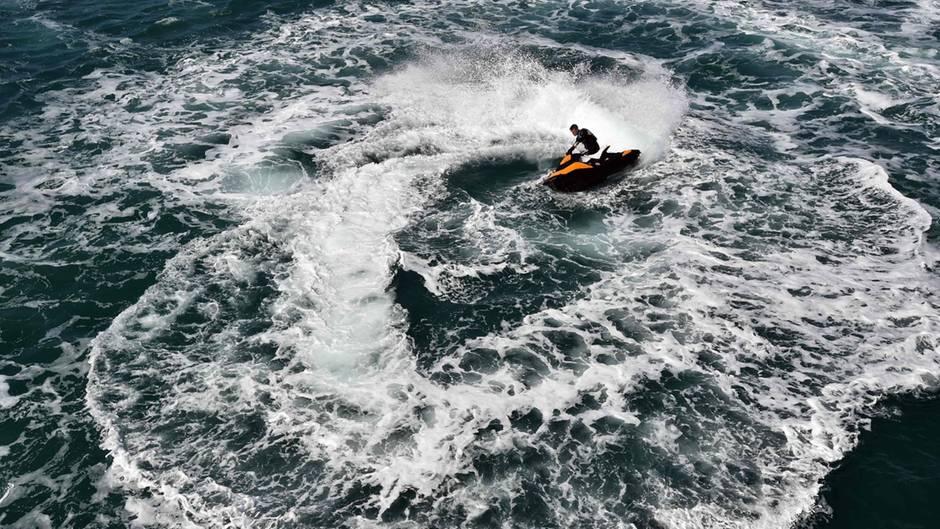 Ein Jet-Ski-Fahrer zieht Kreise auf dem offenen Meer.