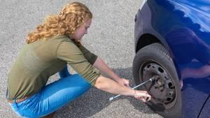 Eine junge Frau löst die Schrauben an einem Autoreifen, um den Reifen zu wechseln