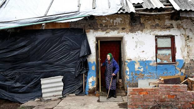 Die blinde Jelena Parschina, 68, tastet sich aus ihrem Haus in Awdijiwka. 2017 wurde das Dach bei einem Angriff zerstört