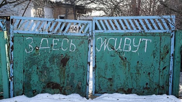 """""""Hier leben Menschen"""", steht auf dem Tor in Opytne.50 Menschen harren in den Ruinen des Dorfes aus."""