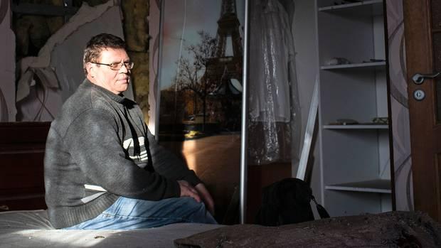Rodion Lebedew auf dem Bett seines Hauses. Nur ein Raum ist bewohnbar.