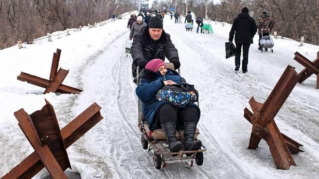 Eine alte Frau mit Gehbeschwerden lässt sich in einem improvisierten Schlitten über die Grenze schieben