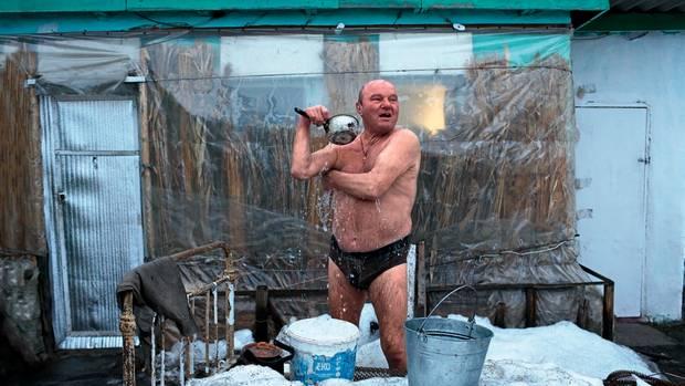 Anatolij Malenik wäscht sich vor seiner Datscha in Staniza Luhanska. Gegen die Kälte dämmte er das Sommerhaus mit Schilf.