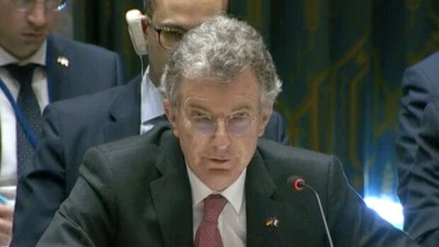 Ein Mann mit kurzen grauen Locken und runder Brille sitzt in Anzug und Krawatte an einem Tisch und spricht in ein Mikrofon
