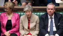 Die britische Premierministerin Theresa May sitzt auf einer grün gepolsterten Bank im britischen Unterhaus