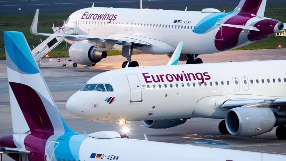 Drei Flugzeuge mit Eurowings-Lackierung stehen unterschiedlich ausgerichtet auf einem Flughafen