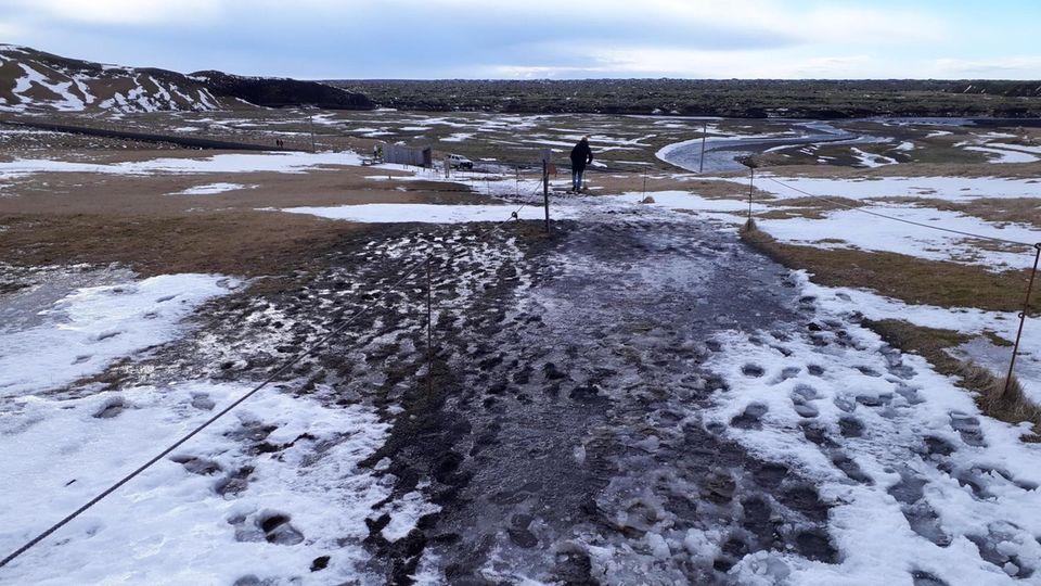 In Schnee und Matsch sind hunderte Schuhabdrücke zu sehen, die zwischen zwei aufgespannten Seilen Richtung Horizont führen