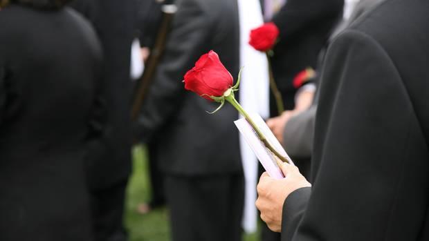 Mann auf Beerdigung mit Rose