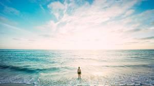 Frau steht am Strand mit Beinen im Wasser