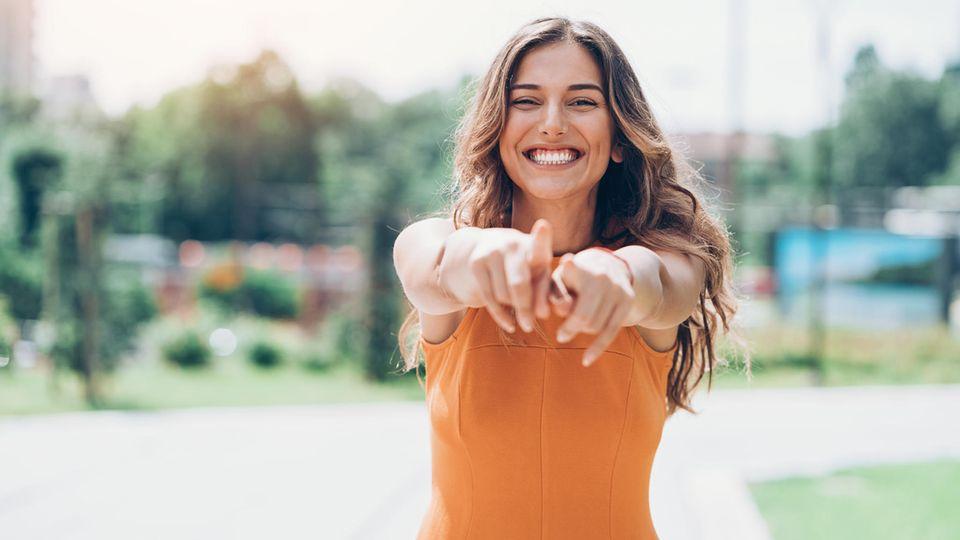 Eine Frau zeigt lachend mit beiden Findern in die Kamera