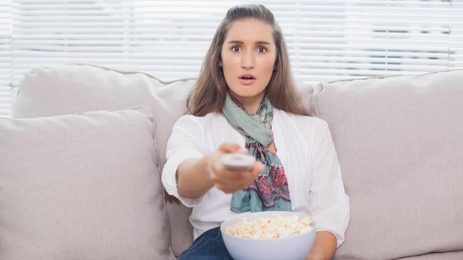 Junge Frau auf dem Sofa mit Popcorn und Fernbedienung